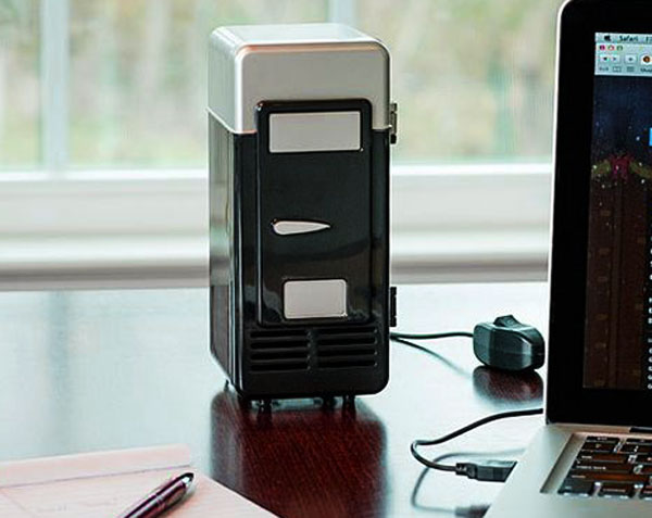 Mini frigo USB noir posé sur un bureau branché au PC