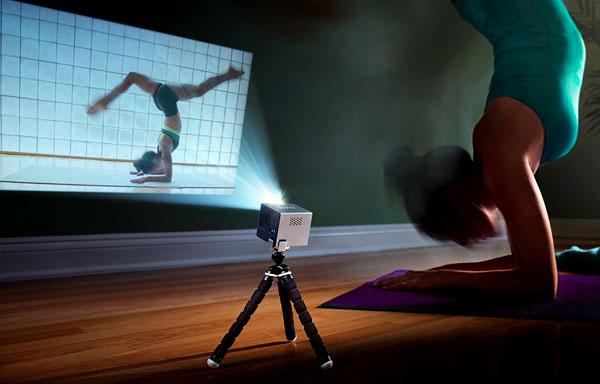 une femme reproduit un mouvement de Yoga diffusé sur son mur grace au mini projecteur Rif6 Cube