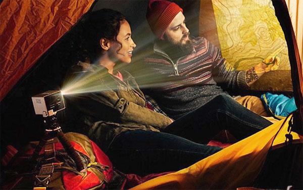 un couple regarde la projection d'un carte dans une tente via le rif6 cube