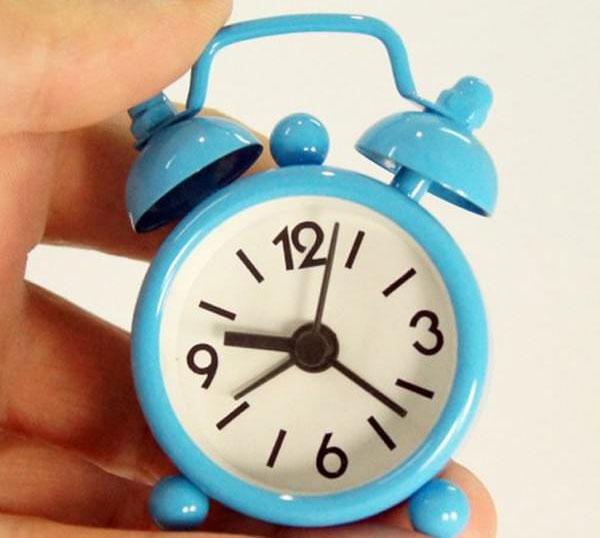 mini réveil bleu tenu entre deux doigts